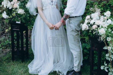 Photo pour Recadrée tir des mariés main dans la main au cours de la cérémonie - image libre de droit