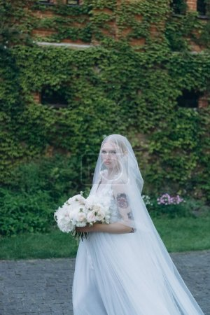 beautiful young bride in garden in front of ancient building covered with vine
