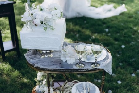 table with wedding cake and glasses of champagne on green grass
