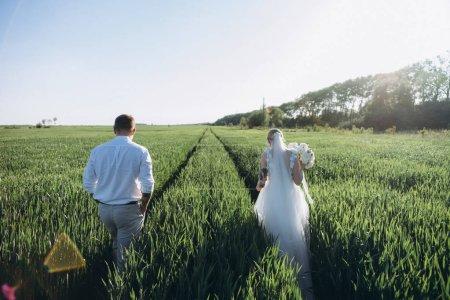 Photo pour Mariée et marié marchant dans le champ agricole au coucher du soleil - image libre de droit