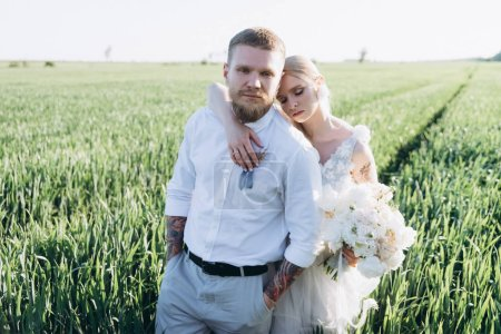 bride and groom embracing in agro field on sunset