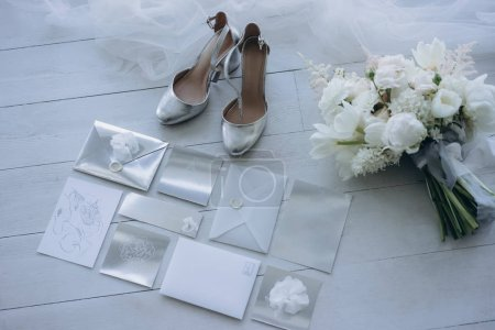 top view of stylish wedding invitations with bridal shoes and bouquet on floor
