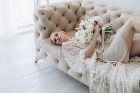 beautiful young woman with white bouquet lying on couch
