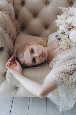 Photo pour Vue grand angle de belle jeune femme avec bouquet blanc couché sur le canapé - image libre de droit