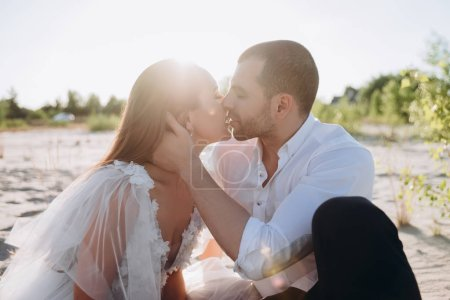 beautiful happy couple kissing on beach with back light
