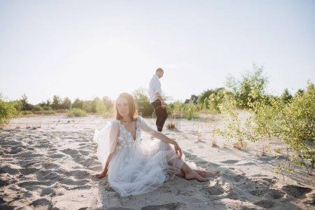 attractive young woman sitting on beach, boyfriend walking behind