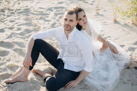 beautiful happy couple sitting on sandy beach