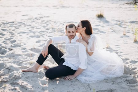 beautiful woman kissing her boyfriend while sitting on beach