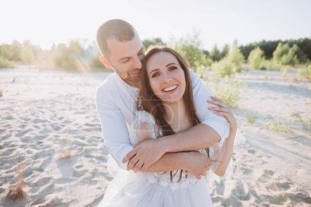 Photo pour Copain étreignant sa petite amie souriante sur la plage - image libre de droit