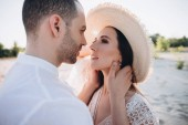 tender man hugging beautiful young woman in hat