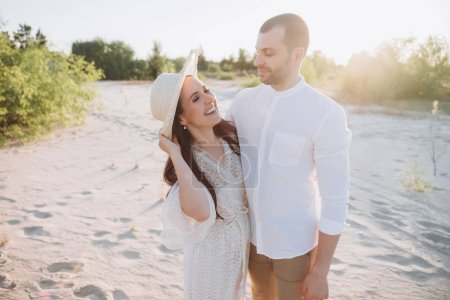 beautiful laughing woman in hat hugging with handsome man on beach