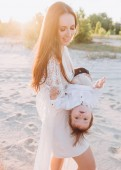 young mother having fun with baby on beach