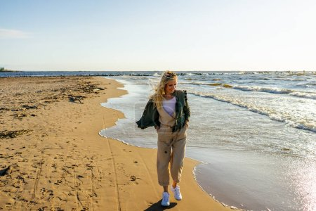 young smiling woman in stylish clothing on seashore on summer day