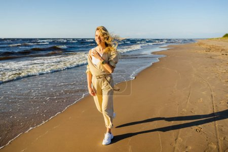 young smiling woman in stylish clothing walking on seashore on summer day