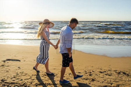 side view of young couple in love holding hands while walking on sandy beach in Riga, Latvia
