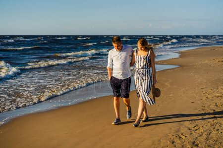 young couple in love hugging and walking on sandy beach in Riga, Latvia