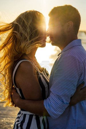 Photo for Side view of beautiful couple in love on seashore during sunset - Royalty Free Image