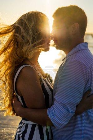 Photo pour Vue latérale d'un beau couple amoureux au bord de la mer au coucher du soleil - image libre de droit