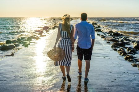 Photo for Back view of couple in love walking on seashore during sunset in Riga, Latvia - Royalty Free Image