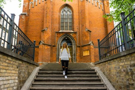 Photo for Young woman walking down steps on street in Riga, Latvia - Royalty Free Image
