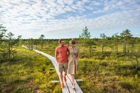 Photo pour Couple souriant amoureux marchant sur un pont en bois avec des plantes vertes et ciel bleu sur le fond - image libre de droit