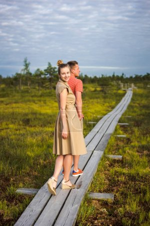 young couple in love holding hands on wooden bridge with green plants on background