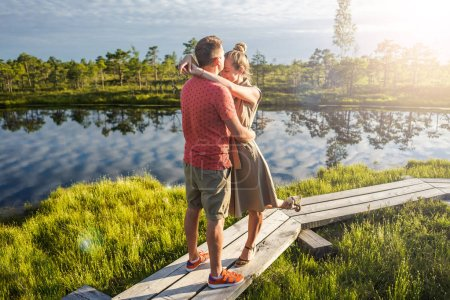 couple in love hugging each other on wooden bridge with green trees and river on background
