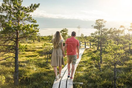 back view of couple in love walking on wooden bridge with blue sky on background
