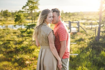 portrait of tender couple in love on wooden bridge with green plants on background