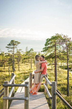 side view of affectionate couple hugging on wooden bridge with green plants and blue sky on background