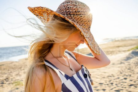 side view of attractive young woman in straw hat on sandy beach in Riga, Latvia
