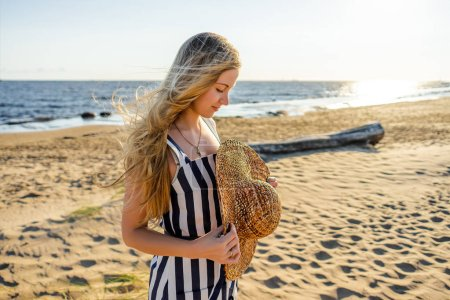 side view of attractive young woman with straw hat on sandy beach in Riga, Latvia