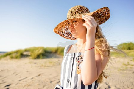portrait of attractive young woman in straw hat on sandy beach in Riga, Latvia