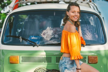 Attractive smiling girl posing by vintage green van on summer day