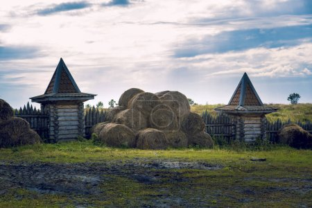 On the manor fenced with a palisade with watchtowers lie bales of hay