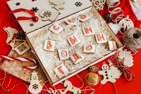 """Box with Christmas gingerbread in the form of letters, folding into the words """" Happy new year!""""."""