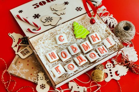 """Photo for Box with Christmas gingerbread in the form of letters, folding into the words """" Happy new year!"""". - Royalty Free Image"""