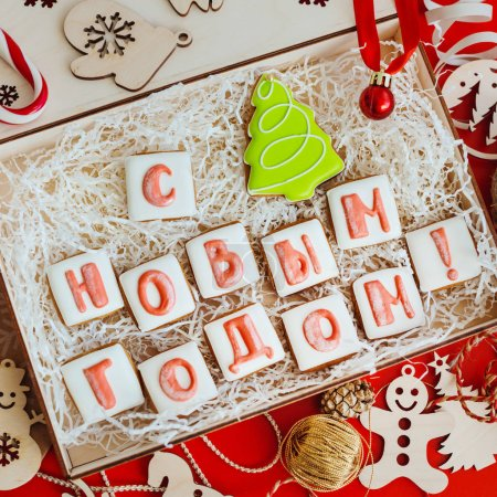 """Photo for Box with Christmas gingerbread in the form of letters, folding into the words """" Happy new year!"""". Top view - Royalty Free Image"""