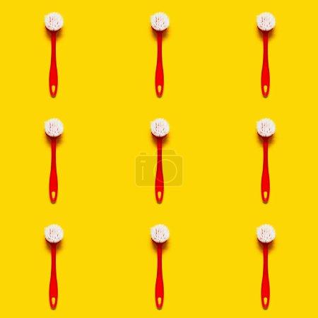 Photo pour Pinceau rouge vif se trouve sur un fond jaune clair. Dans le style pop art. Vue de dessus. Espace copie. - image libre de droit
