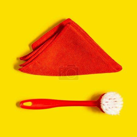 Photo pour Une brosse de lavage de vaisselle rouge et un chiffon microfibre rouge se trouvent sur un fond jaune clair. Style pop art. Vue de dessus. - image libre de droit