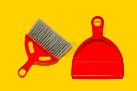 Photo for Red dustpan and brush lying on yellow background. In the style of pop art. Top view. - Royalty Free Image