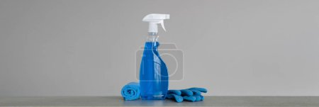 Photo for Cleaning blue spray bottle with plastic dispenser, marigolds and cloth for dust  on grey background. Cleaning tools. Copy space. - Royalty Free Image