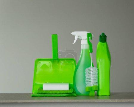 Photo pour Bouteille de détergent verte pour toilettes, vaporisateur, brosse, éponge, cuillère et poussière sur fond gris. Outils de nettoyage . - image libre de droit