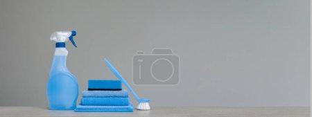 Photo pour Nettoyage vaporisateur bleu avec distributeur en plastique, éponge, frotter la brosse pour vaisselle et chiffon à poussière sur fond gris. Outils de nettoyage. Espace copie. - image libre de droit