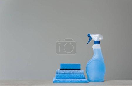 Photo pour Nettoyant pulvérisateur bleu avec distributeur en plastique, éponge et chiffon à poussière sur fond gris. Outils de nettoyage. Espace copie. - image libre de droit