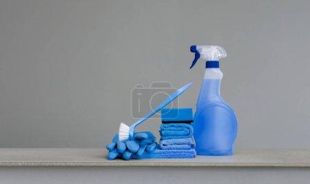 Photo pour Nettoyage vaporisateur bleu avec distributeur en plastique, éponge, balai-brosse pour plat, chiffon pour les gants de caoutchouc et de poussière sur fond gris. Équipement de nettoyage. Espace copie. - image libre de droit