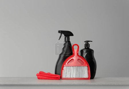 Photo for Black cleaning products and red cleaning tools on neutral background. Copy space. - Royalty Free Image