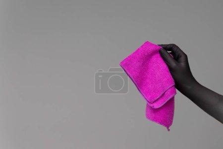 Photo pour Un coup de main dans un gant de caoutchouc est titulaire d'un chiffon en microfibre brillant sur un fond neutre. Concept de printemps lumineux, nettoyage de printemps. - image libre de droit