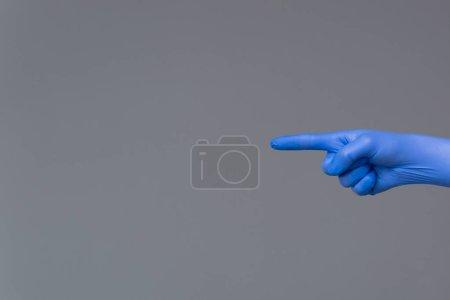 Photo pour La main dans des points de gant en caoutchouc vers la gauche avec index. Fond neutre, espace copie. - image libre de droit