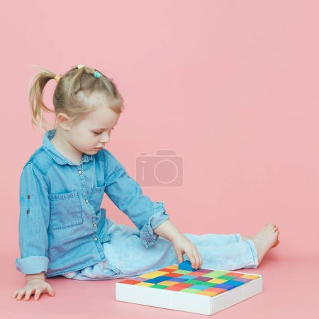 A charming little girl in denim clothes on a pink background puts wooden multi-colored cubes in a white box. Copy space.